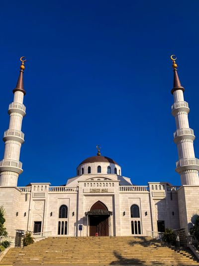 Low angle view of historic mosque against clear blue sky