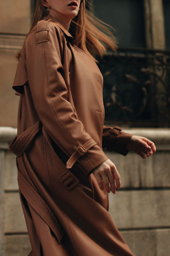Cropped figure of woman in stylish autumn brown coat. street casual fashion concept