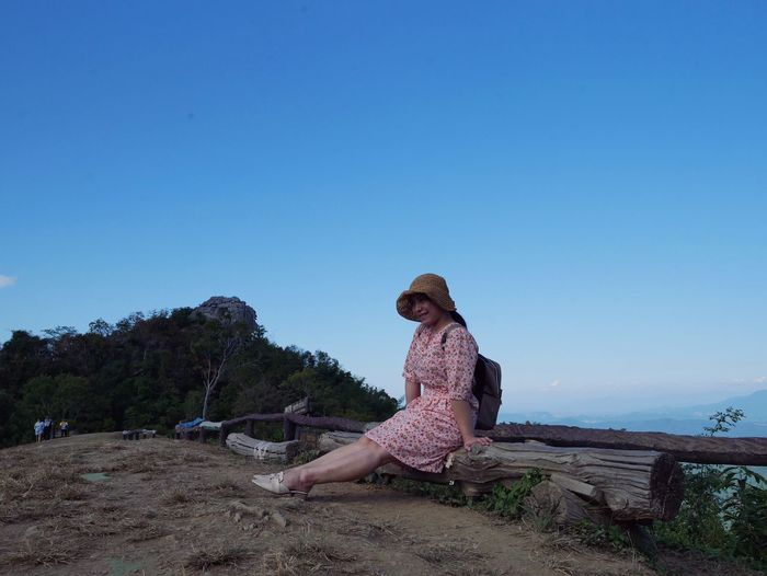 Woman sitting on land against clear blue sky