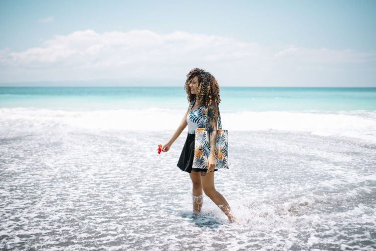 Woman with curly hair standing at beach