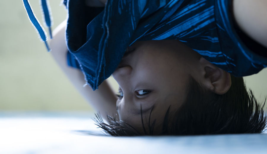Close-up portrait of boy doing headstand