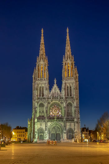 View of illuminated church of saint peter and saint paul in ostend against blue sky at night
