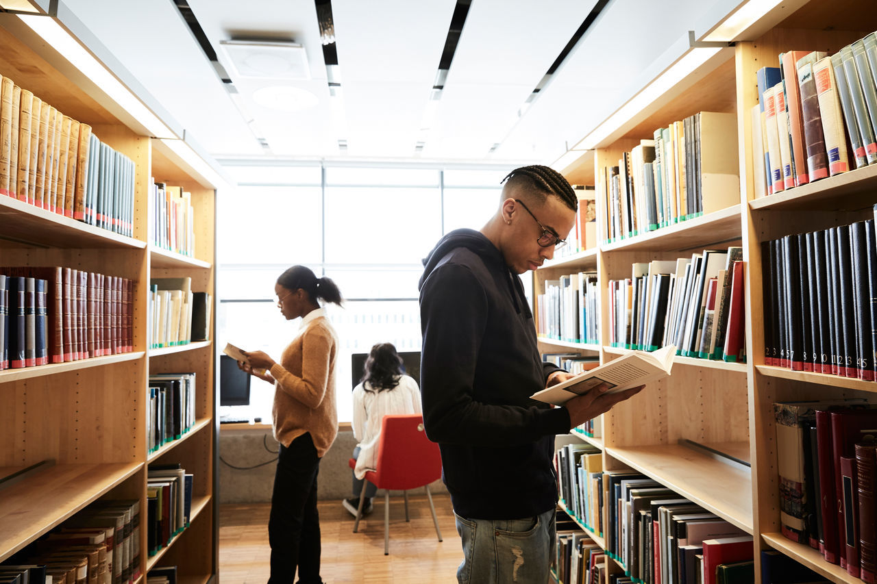 Male and female friends reading book while woman using computer in library at university