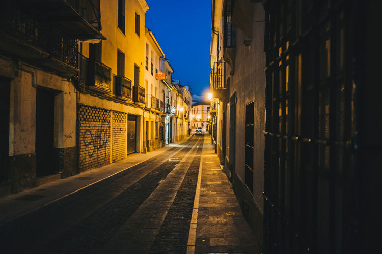 Empty Road Amidst Buildings In City At Night