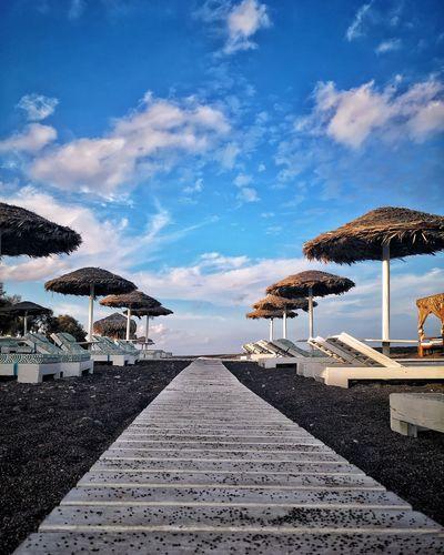 Beach umbrellas by sea against sky