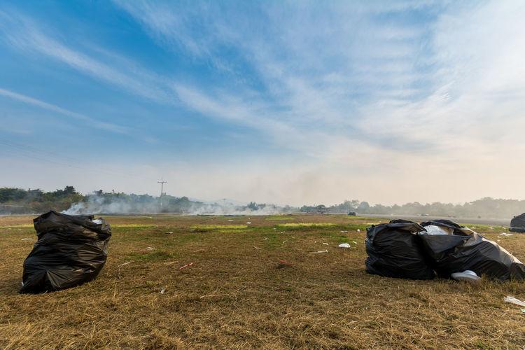 Garbage bags on field against sky