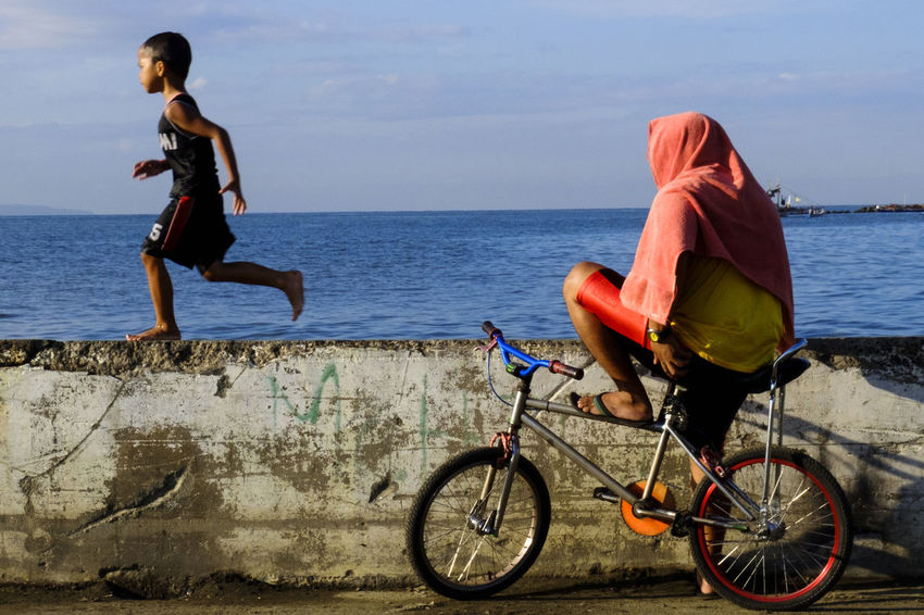 Bicycle Day EyeEm Best Shots Eyeem Philippines Horizon Over Water Mode Of Transport Outdoors People Real People Sea Sky Street Photography Streetphotography Towel Animal Transportation Waiting Game Water
