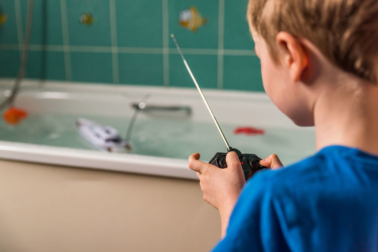 Blond boy with British flag on blue Tshirt playing with radio controlled boat in bathroom Bath British Radio Bathroom Blond Boat Boy Boys Childhood Close-up Controlled Day Education Headshot Indoors  Learning One Boy Only One Person People Playing Real People Toy Water Go Higher