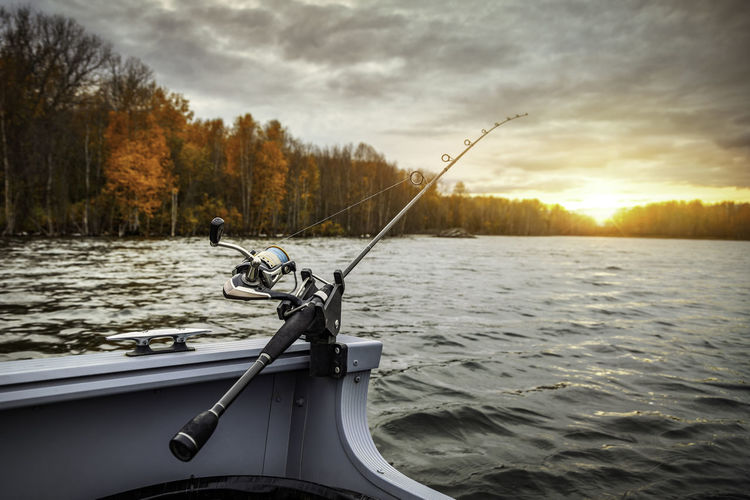 Fishing rod on river against sky at sunset