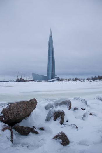 Seaside Skyscraper Tower Rock - Object Cityscape Clouds Cityscape Water Snow Cold Temperature Winter Polar Climate Sunset Fog Lake Frozen Water Office Building Extreme Weather Frozen Deep Snow Atmospheric Mood
