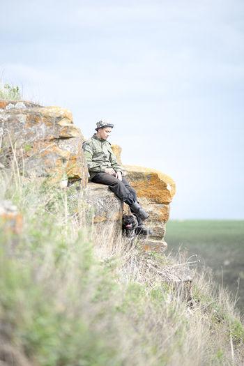 Man sitting on mountain against sky
