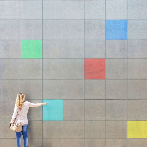 Rear View Of Woman Touching Colorful Wall
