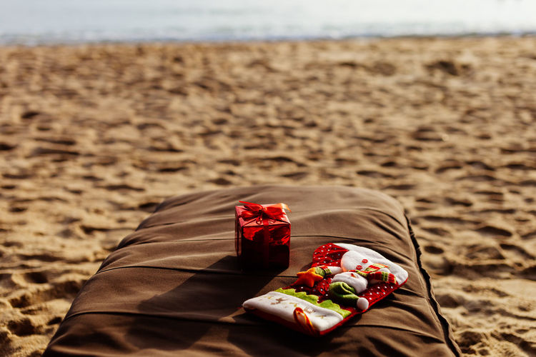 High angle view of christmas presents on pillow at beach
