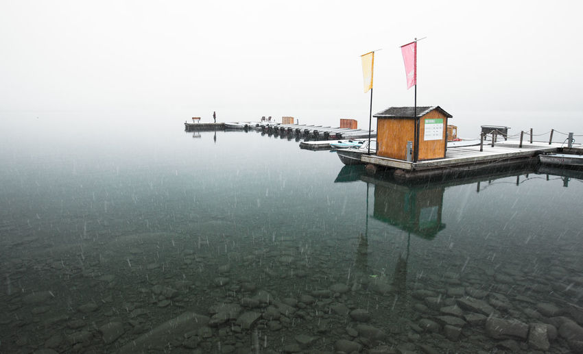 Water Architecture Fog Built Structure Nature Building Exterior Sky Reflection Day Waterfront Lake Wood - Material Nautical Vessel Tranquility Scenics - Nature Outdoors Wooden Post Pier Winter Snowing One Person