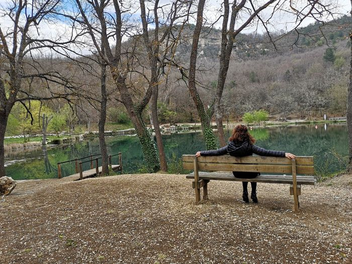 Tree Sitting Bench Seat Plant One Person Nature Water Leisure Activity Real People Day Lifestyles Lake Full Length Relaxation Park Adult Tranquility Outdoors Park Bench Warm Clothing Sinizzo Woman