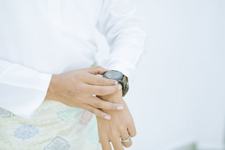 Midsection of man holding wrist watch