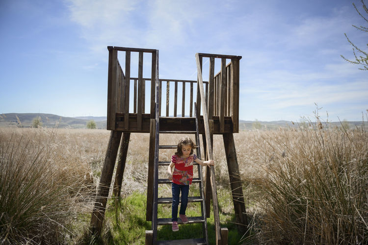 Little girl climbing to a wooden observation tower in a wetland in Padul, Granada, Andalusia, Spain Nature Casual Clothing Child Childhood Countryside Day Females Field Full Length Girl Girls Grass Innocence Land Landscape Leisure Activity Little Nature One Person Outdoors Plant Real People Sky Standing Women