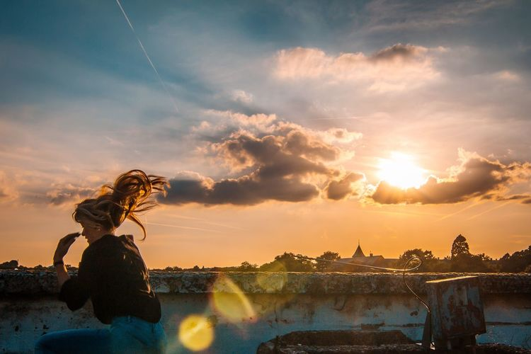 Woman With Tousled Hair Crouching By Retaining Wall Against Dramatic Sky During Sunset