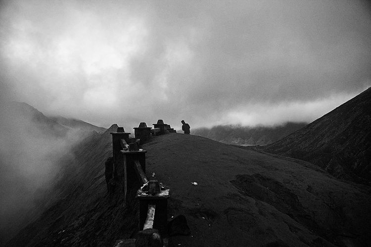 People photographing on mountain against sky