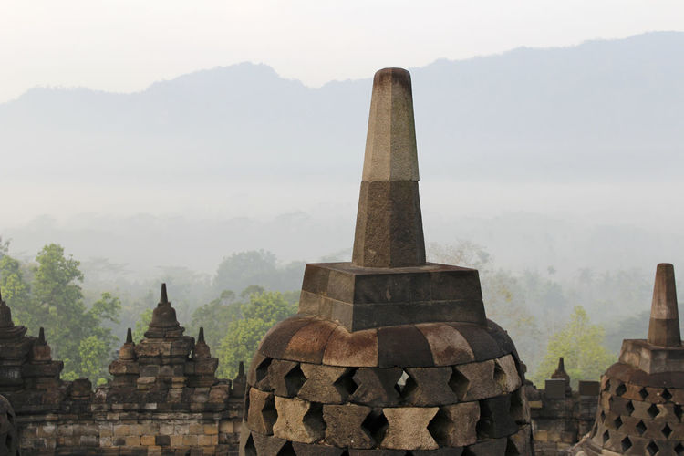 Borobudur Temple with the mysteries forest surrounding during sunrise, Yogyakarta, Indonesia Yogyakarta Ancient Ancient Civilization Architecture Belief Borobudur Buddhist Temple Building Exterior Built Structure Fog Forest History No People Outdoors Place Of Worship Religion Spirituality Stone Material Sunrise The Past Tourism Travel Travel Destinations