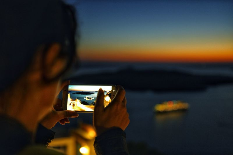 Close-up of woman photographing sea during sunset