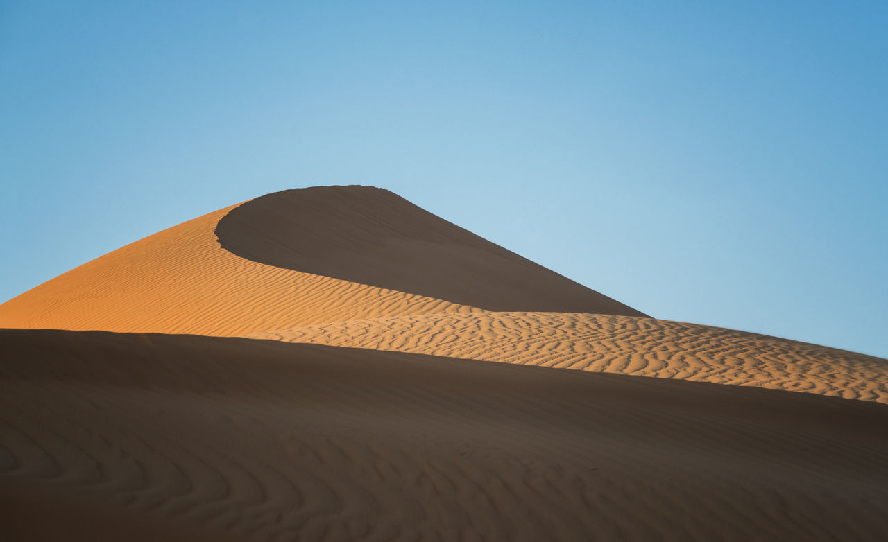 Low Angle View Of Sand Dunes Against Clear Blue Sky