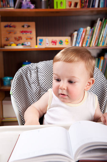 Cute baby boy with book on table at home