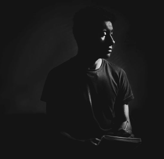 Young man holding diary looking away while sitting against black background