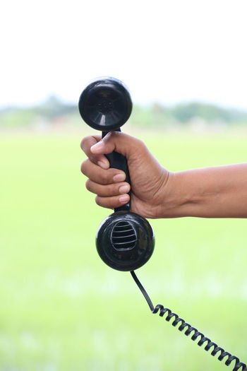 Close-up of hand holding telephone against sky