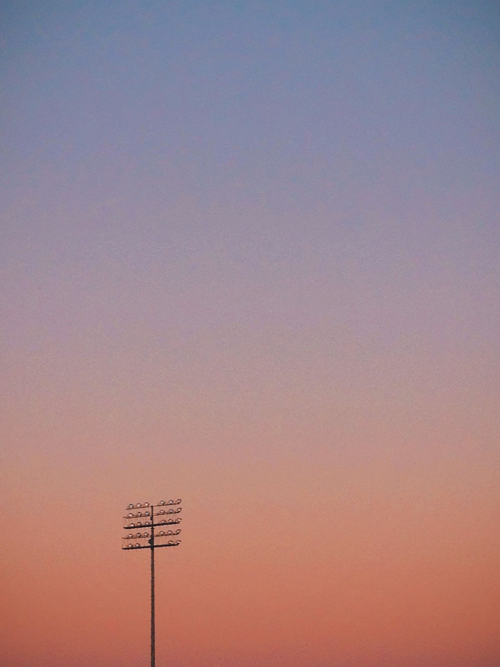 copy space, clear sky, sunset, low angle view, orange color, outdoors, no people, silhouette, nature, technology, sky, communication, high section, tranquility, beauty in nature, scenics, street light, transportation, dusk, lighting equipment