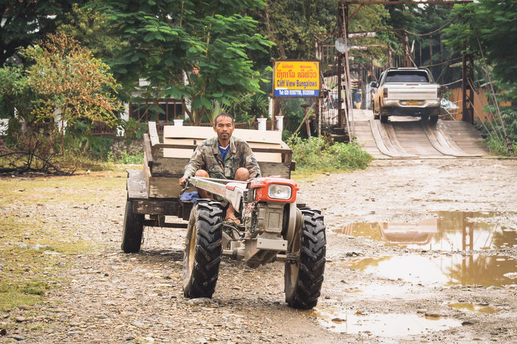 Man driving tractor on a rural road in Vang Vieng, Laos. Adult ASIA Asian  Country Countryside Culture Driving Land Laos Lies Man Mode Of Transport Outdoors People People Watching Real People Road Rural Street Thailand Tractor Traditional Transportation Travel Vang Vieng