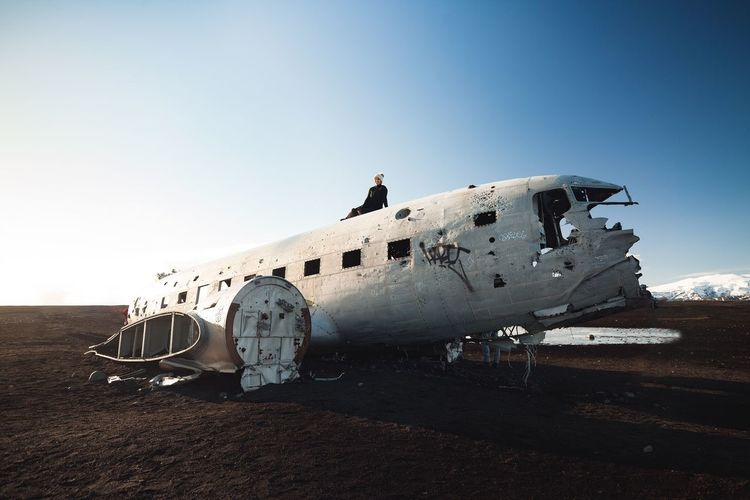 Woman Sitting On Abandoned Airplane Over Field Against Sky