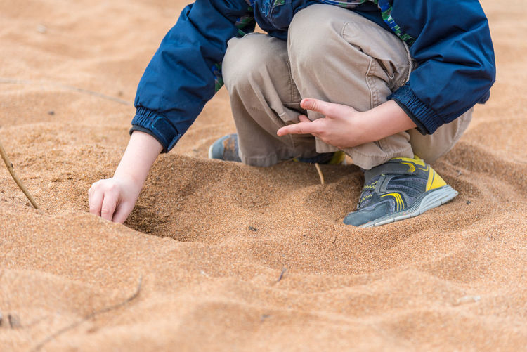 Low Section Of Boy Playing On Sand