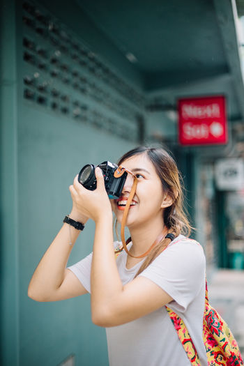Fashion Accessories Activity Adult Beautiful Woman Camera - Photographic Equipment Casual Clothing Focus On Foreground Hair Hairstyle Holding Leisure Activity Lifestyles One Person Outdoors Photographer Photographing Photography Themes Real People Smiling Standing Waist Up Women Young Adult Young Women