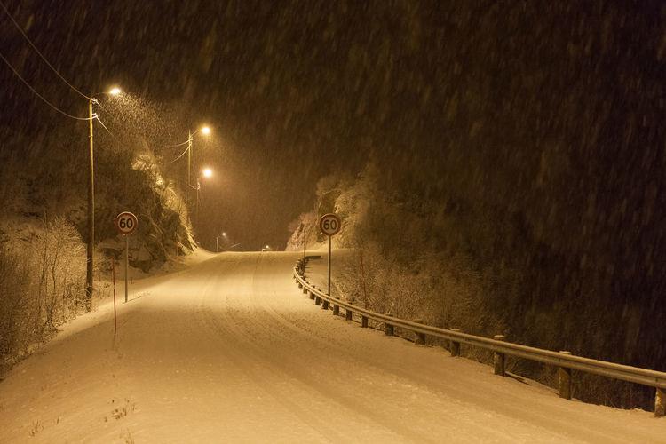 Illuminated snow covered road at night