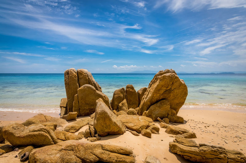 A veiw of golden rocks protruding from a golden sand beach of the Perhentian Islands, Malaysia. Beach Beauty In Nature Cloud - Sky Horizon Horizon Over Water Idyllic Land Nature No People Remote Rock Rock - Object Sand Scenics - Nature Sea Sky Solid Tranquil Scene Tranquility Water