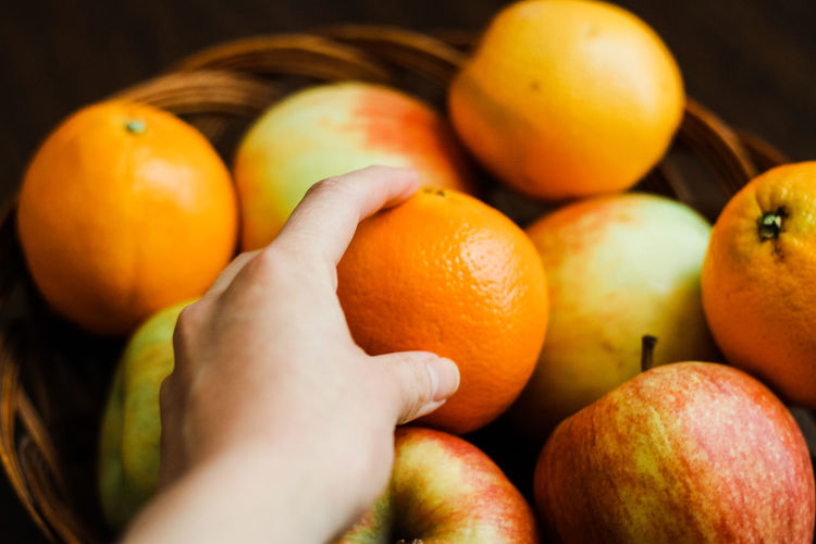 A woman's hand reaches into a wicker basket full of apples and oranges Food And Drink Food Healthy Eating Wellbeing Fruit Orange Color Freshness Orange - Fruit Orange Human Body Part Human Hand Hand One Person Citrus Fruit Close-up Holding Ripe Finger Healthy Lifestyle Healthy Food Fruit Bowl Wicker Basket Apple Wellness Personal Perspective