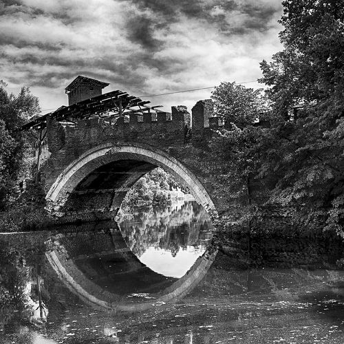 Arch bridge against cloudy sky
