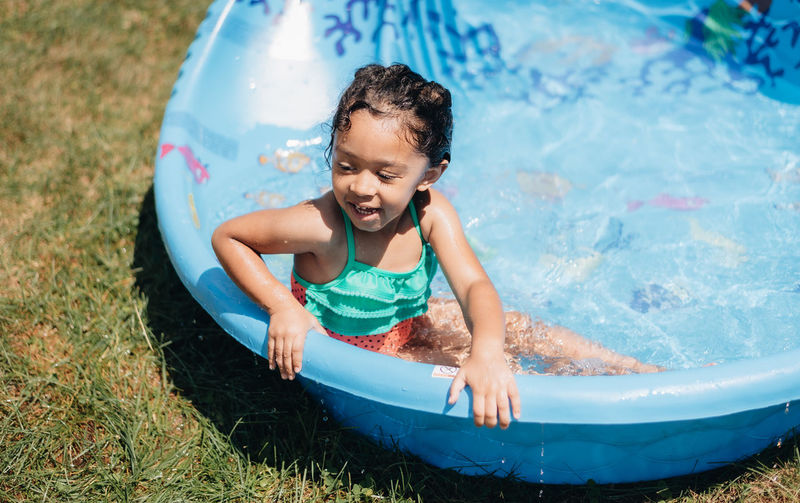 Cute smiling girl sitting in wading pool outdoors