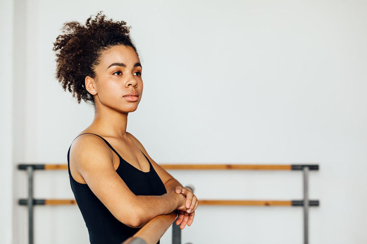Young woman looking away while standing by railing in studio