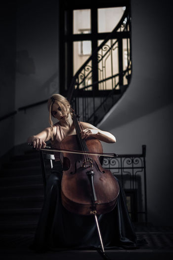Young woman playing cello at home