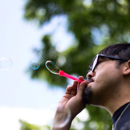 Blowing Bubble Wand One Person Eyeglasses  Bubble Real People Focus On Foreground Leisure Activity Mid-air Headshot Lifestyles Outdoors Day Fragility Young Adult Close-up Tree People