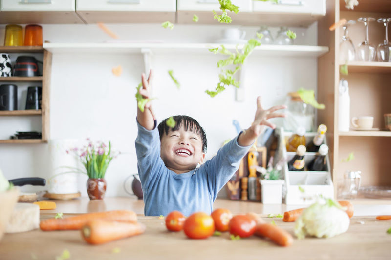 Happy Boy Tossing Vegetables In Kitchen At Home