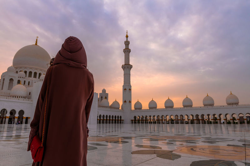Rear view of woman standing at historic mosque against cloudy sky
