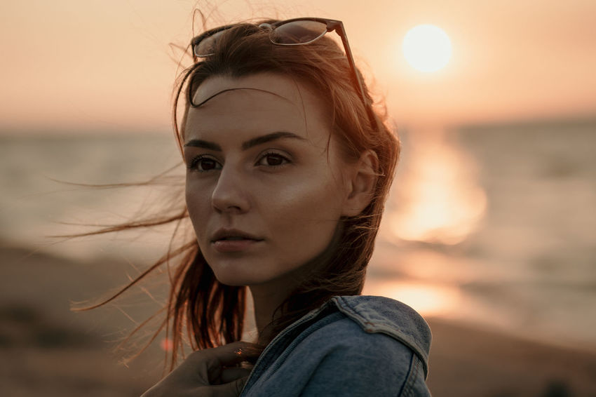 Beautiful Woman Contemplation Focus On Foreground Hair Hairstyle Headshot Leisure Activity Lifestyles Looking At Camera Nature One Person Outdoors Portrait Real People Sea Sky Sunset Water Women Young Adult A New Beginning