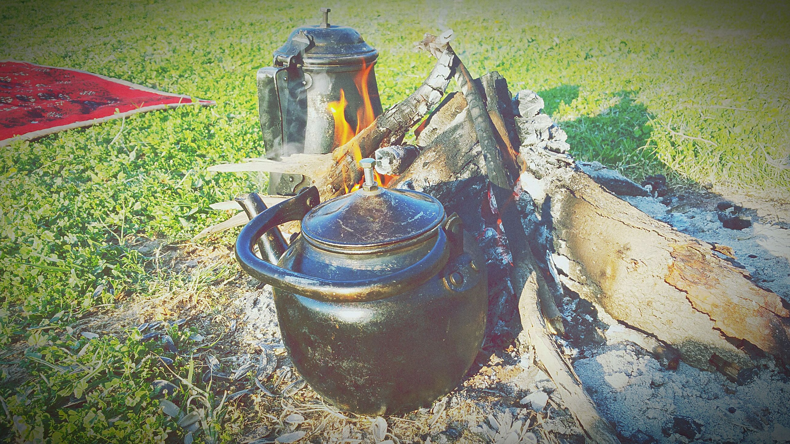 container, land, nature, field, grass, day, metal, plant, no people, outdoors, bucket, high angle view, old, burning, preparation, environment, heat - temperature, landscape, fire, rural scene