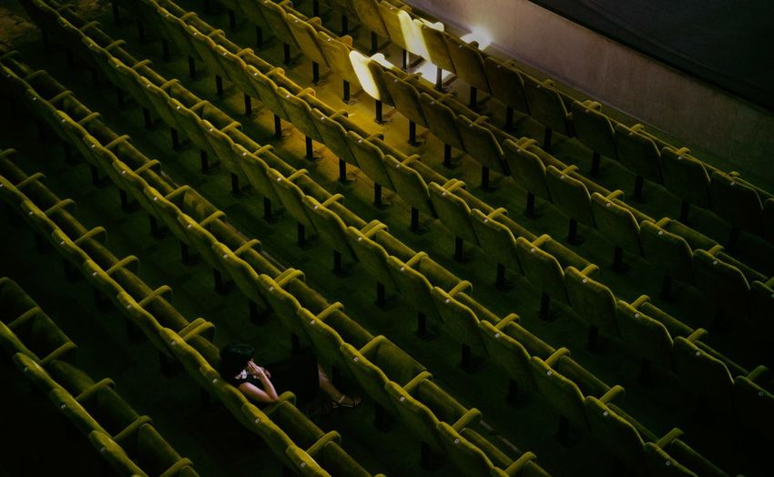 High angle view of woman sitting on chair in theater