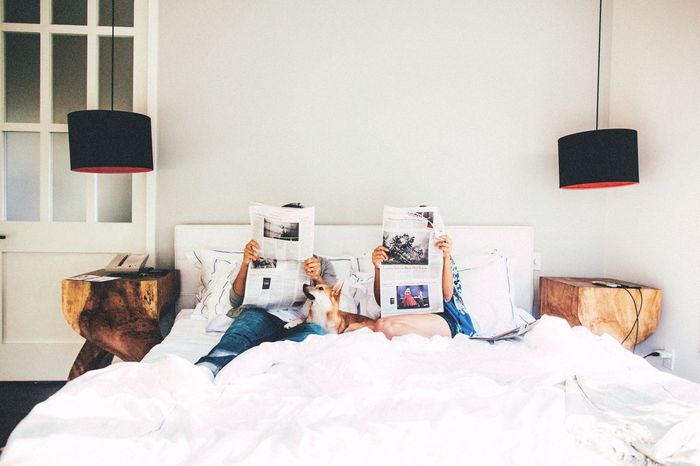 Couple reading newspaper while sitting on bed at home