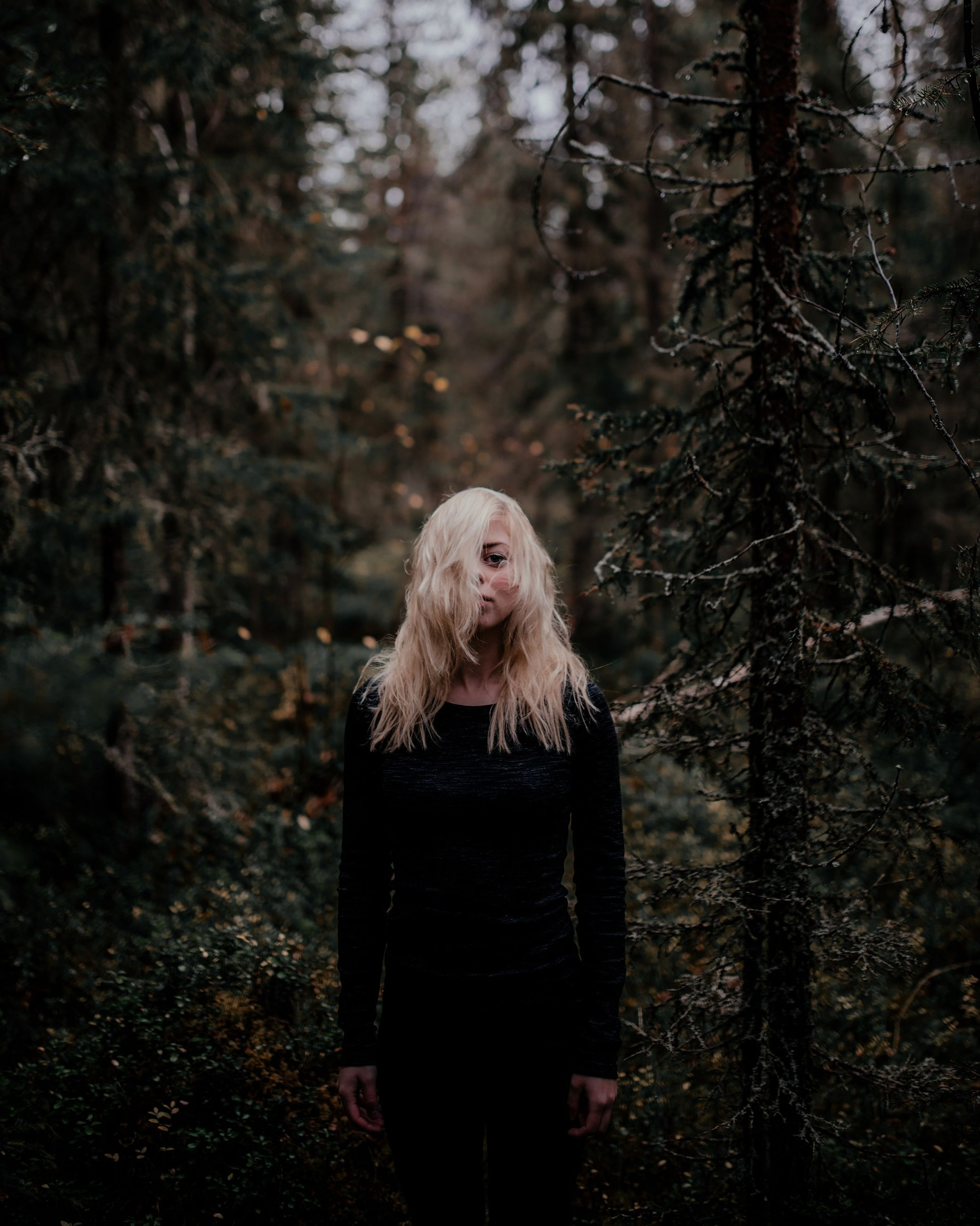 tree, forest, blond hair, hair, one person, long hair, hairstyle, young adult, land, standing, young women, three quarter length, front view, real people, leisure activity, nature, plant, women, woodland, outdoors, beautiful woman, contemplation, warm clothing