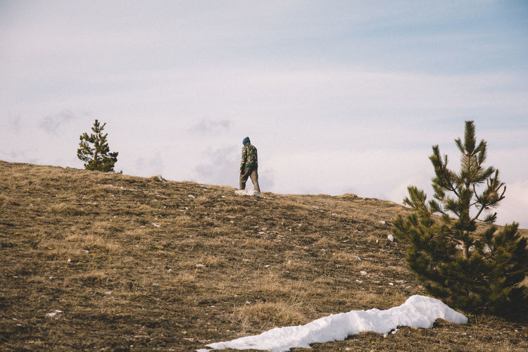Rear view of man walking on hill against sky